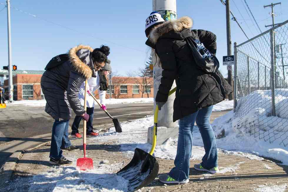GVSU students shoveling snow off a sidewalk